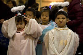 Children dressed as angels take part in a mass on the eve of Christmas at the South Cathedral official Catholic church in Beijing, China, Wednesday, Dec. 24, 2014.