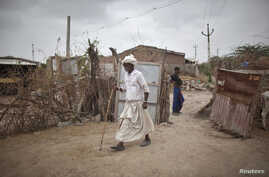 A farmer walks through the entrance of his house at Sami village in the western Indian state of Gujarat in this August 6, 2012, file photo.