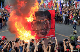 Protesters burn a cube effigy with a face of President Rodrigo Duterte during a National Day of Protest outside the presidential palace in metro Manila, Philippines September 21, 2017.
