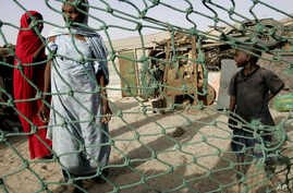 FILE - People stand outside their home in a poor neighborhood of Nouakchott, Mauritania, where a landmark law was passed on Aug. 8, 2007 to jail anyone who keeps slaves.