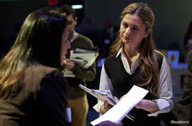 """A woman speaks to a potential employer at the """"Hiring Our Heroes"""" job fair at the Intrepid Sea, Air and Space Museum in New York March 28, 2012. The job fair, which included employers including JP Morgan Chase, FedEx and the New Jersey State Police d"""