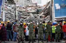 Rescue workers and volunteers stand in the middle of the street after an earthquake alarm sounded and a small tremor was felt during rescue operations at the site of a collapsed building in Roma Norte, in Mexico City, Saturday, Sept. 23, 2017.