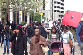 """A few hundred protesters looping the plaza and chanting """"all night all day we want justice for Freddie Gray,"""" in Baltimore, Maryland, April 23, 2015 (VOA / V. Macchi)"""