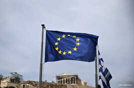 A European Union flag flutters as the ancient Parthenon temple is seen in the background in Athens, June 1, 2015.