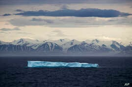 FILE - An iceberg floats past Bylot Island in the Canadian Arctic Archipelago, July 24, 2017.