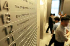 FILE - Employees of Korea Hydro & Nuclear Power Co. walk inside the company's Seoul office after prosecutors seized documents and computer hard drives in South Korea.