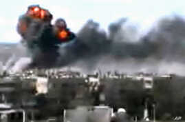 This video image taken from amateur video and broadcast by Bambuser/Homslive shows a series of devastating explosions rocking the central Syrian city of Homs, Syria, June 11, 2012.