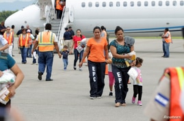 A handout provided by the Honduran Presidential House shows women and children walking on the tarmac after being deported from the U.S., at the Ramon Villeda international airport in San Pedro Sula, July 14, 2014.
