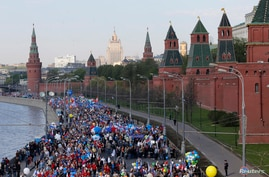 People walk with flags and banners past the Kremlin during a rally in Moscow, May 1, 2014.