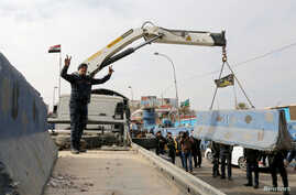 Iraqi security forces lift concrete blockades in order to remove checkpoints in Iraq's capital of Baghdad, Dec. 20, 2016.