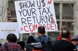 """Tax FILE - A woman in Seattle holds a sign during a rally that reads """"Show us your tax returns, Comrade"""" in reference to calls for President Donald Trump to release his tax returns and his alleged ties to Russia, April 15, 2017."""