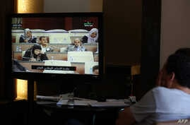 Reporters watch a live feed of Libyan members of parliament meeting to decide on a prime minister, May 4, 2014.