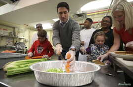 FILE - Liberal leader Justin Trudeau helps prepare Thanksgiving dinner with his son Xavier, bottom left, and daughter Ella-Grace, bottom right, at the Salvation Army in Ottawa, Ontario, Oct. 11, 2015.