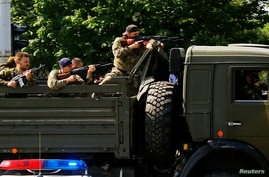 FILE - A military truck with armed pro-Russian rebels is seen driving through a police check-point towards the airport of the eastern Ukrainian city of Donetsk May 26, 2014.