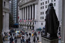 People stand near a statue of George Washington, adjacent to the New York Stock Exchange, background, Dec. 22, 2018, at the closed Federal Hall National Memorial in New York. The partial shutdown of the government that began Saturday has added anothe