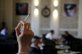 FILE: A woman holds a cigarette in a cafe in Vienna, Austria.