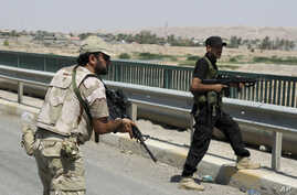 Iraqi security forces and Shiite militiamen patrol in Amirli, about 170 kilometers (105 miles) north of Baghdad, Iraq, Aug. 31, 2014.