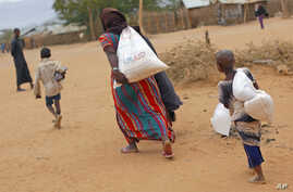 A newly arrived Somali family carry their supply of aid outside Dadaab, Eastern Kenya, 100 kms (60 miles) from the Somali border, Aug. 5, 2011. (AP)