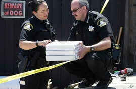T. Abbott, left, and John Lopes from the Sacramento County Sheriff's crime scene investigation office discuss boxes of evidence gathered from the home of murder suspect Joseph DeAngelo, April 26, 2018, in Citrus Heights, Calif.