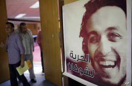 Journalists walk past a poster showing jailed Egyptian photojournalist Mahmoud Abou-Zeid, known by his nickname Shawkan at the press syndicate in Cairo, Egypt, Aug. 12, 2015. He's been locked up without any charges for covering the Rabaa massacre in