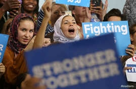 FILE - Young Muslim women listen to Democratic presidential candidate Hillary Clinton speak at a voter registration rally in Detroit, Michigan, Oct. 10, 2016. Out of some 3.3 million Muslims living in America, about 1.5 million are eligible to vote,