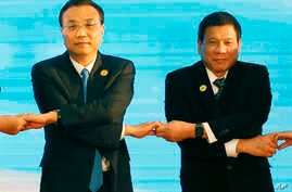 FILE - In this Sept. 7, 2016, photo, Chinese Premier Li Keqiang (L) and Philippine President Rodrigo Duterte link arms during the ASEAN Plus Three summit in Vientiane, Laos. After lashing out at longtime ally America, Duterte is making a state visit
