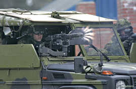 FILE - A Danish soldier fires his machine gun from a vehicle during the NATO Response Force exercise during the NATO Response Force exercise at Oksbol, western Jutland, Denmark, May 16, 2007.