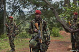 FILE - Troops from the Central African Republic stand guard at a building used for joint meetings where U.S. special forces have paired up with local troops and Ugandan soldiers to seek out Joseph Kony's Lord's Resistance Army, in Obo, Central Africa