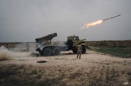 FILE - A rocket is fired from a rocket launcher outside Makhmour, about 75 km (47 miles) east of Mosul, Iraq, March 25, 2016.