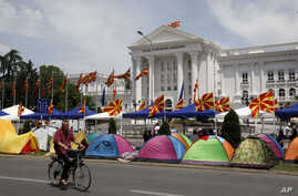 A man on a bicycle passes by tents, posted by the opposition supporters, in front of the government building in Skopje, Macedonia, May 19, 2015.