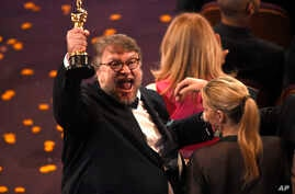 """Guillermo del Toro, winner of the award for best director for """"The Shape of Water"""" celebrates in the audience at the Oscars, March 4, 2018."""