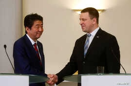 Estonian Prime Minister Juri Ratas shakes hands with Japanese Prime Minister Shinzo Abe, in Tallinn, Estonia, Jan. 12, 2018.