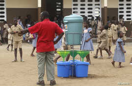 Pupils stand near buckets of water to wash their hands with placed as a preventive measure against Ebola at Anono school in Abidjan Sept. 25, 2014.