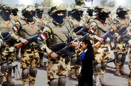 A visitor walks past a banner displaying Egyptian commandos during the first arms fair organized in Cairo, Egypt, Monday, Dec. 3, 2018. Egypt's President Abdel-Fattah el-Sissi inaugurated the fair, where hundreds of companies are participating.
