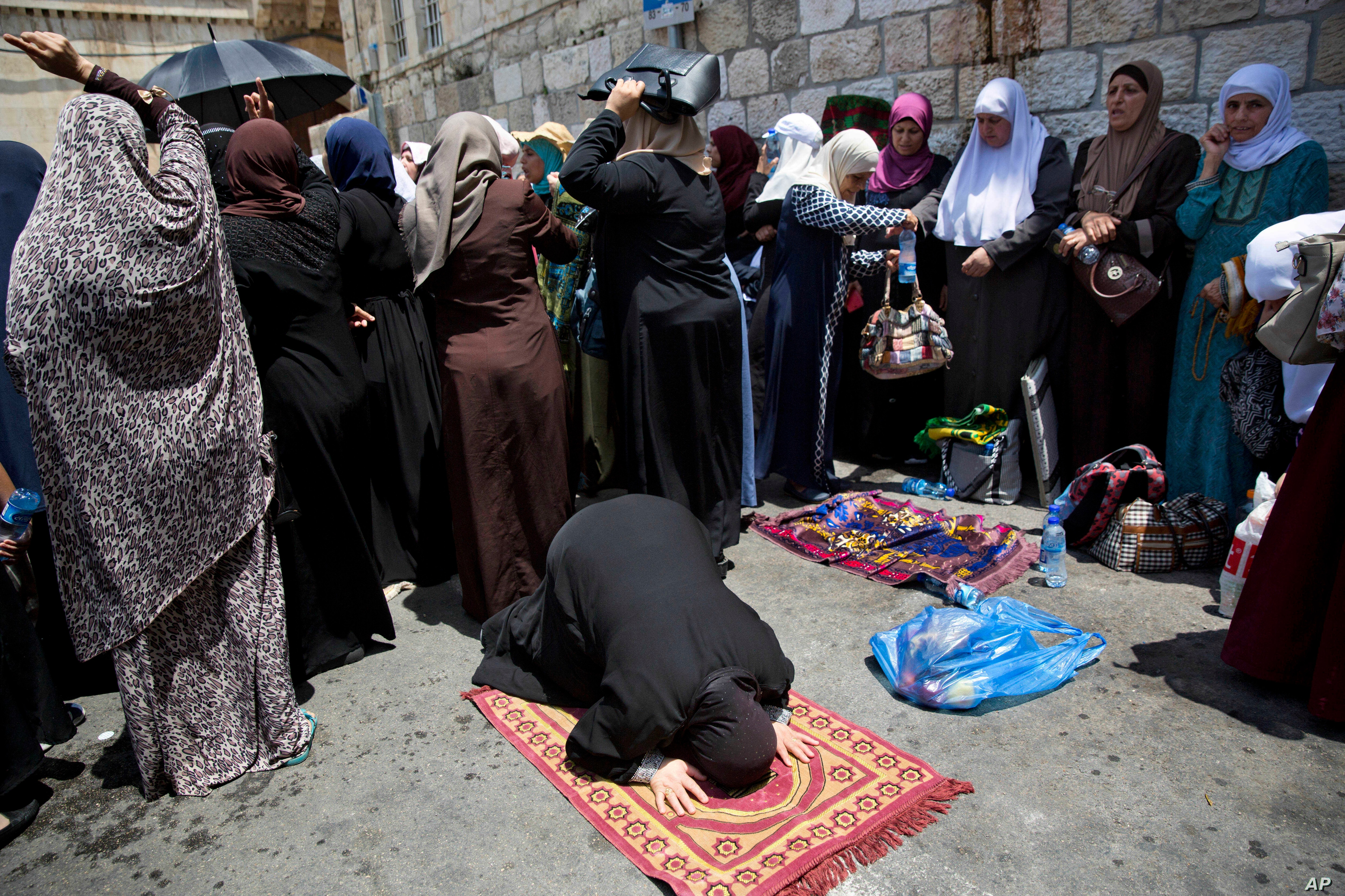 Palestinians women pray at the Lion's Gate following an appeal from clerics to pray in the streets instead of inside the Al Aqsa Mosque compound, in Jerusalem's Old City, Tuesday, July 25, 2017.
