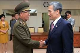 In this photo provided by the South Korean Unification Ministry, South Korean presidential security adviser Kim Kwan-jin, right, shakes hands with Hwang Pyong So, North Korea's top political officer for the Korean People's Army, after their meeting a