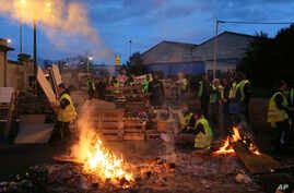 Demonstrators stand in front of a makeshift barricade set up by the so-called yellow jackets to block the entrance of a fuel depot in Le Mans, western France, Tuesday, Dec. 5, 2018.