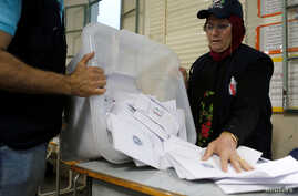 A Lebanese election official empties a ballot box after the polling station closed during Lebanon's parliamentary election, in Beirut, Lebanon, May 6, 2018.