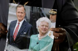 FILE - Lucy Orlando from Florida hold up a photo of Former President George H. W. Bush and his wife Barbara Bush as she waits for the visitation of the former first lady, April 20, 2018, in Houston, Texas.