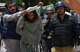 A follower of preacher Tahir-ul-Qadri  is detained by Pakistani policemen during clashes in Lahore, June 17, 2014.