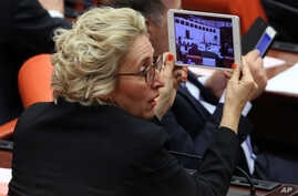 FILE - Melda Onur, an opposition Republican People's Party lawmaker, records debates during a special session of the parliament in Ankara, Turkey, March 19, 2014.