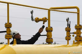 FILE - A worker makes the final checks of the new gas inter connector linking Poland and the Czech Republic before its opening in Cieszyn, Poland, Sept. 14, 2011.