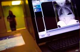 FILE- In this Feb. 9, 2018, photo, a radiology technician looks at a chest X-ray of a child suffering from flu symptoms at Upson Regional Medical Center in Thomaston, Ga.  The Trump administration is quietly trying to weaken radiation rules, relying