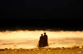 FILE - two veiled Saudi women enjoy the Red Sea at night, in Jiddah, Saudi Arabia, Dec. 26, 2007. Saudi Arabia is planning to build a semi-autonomous luxury travel destination along its Red Sea coast that visitors can reach without a visa. The Red Se