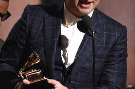 """Sam Smith accepts the award for record of the year for """"Stay With Me"""" at the 57th annual Grammy Awards."""