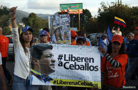 """FILE - Patricia de Ceballos, left, wife of jailed former Mayor Daniel Ceballos, stands next to a banner reading """"Release Ceballos"""" while campaigning to become mayor herself in San Cristobal, Venezuela, May 23, 2014."""