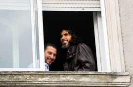 FILE - In this June 5, 2015 file photo, Abu Wa'el Dhiab, from Syria, right, and Adel bin Muhammad El Ouerghi, of Tunisia, both freed Guantanamo Bay detainees, look out the window of their shared home in Montevideo, Uruguay. Abu Wa'el Dhiab, who disap