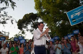 Spain's acting Prime Minister and Popular Party candidate, Mariano Rajoy applauds in front of party supporters during a campaign rally in Seville, Spain, Thursday June 23, 2016.