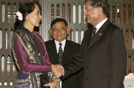 Myanmar's opposition leader Aung San Suu Kyi, left, shakes hands with Thai Deputy Prime Minister Chalerm Yubumrung during their meeting at Government House in Bangkok, Thailand, May 31, 2012.