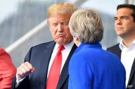 U.S. President Donald Trump, left, clenches a fist when talking to British Prime Minister Theresa May during a summit of heads of state and government at NATO headquarters in Brussels on Wednesday, July 11, 2018. NATO leaders gather in Brussels for a